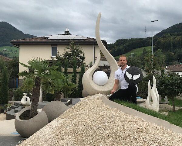 Künstler Roman Stoni mit Urne vor Skulpturen Ausstellung