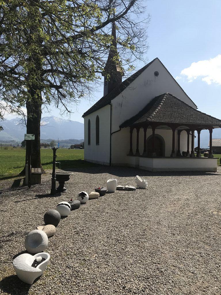 Diverse Urnen für Menschen auf Kies vor Kapelle
