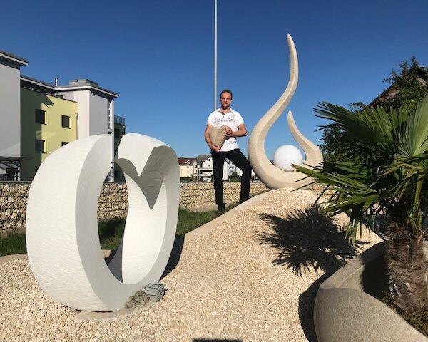 Künstler Roman Stoni mit Urne vor Ausstellung Skulpturen aussen